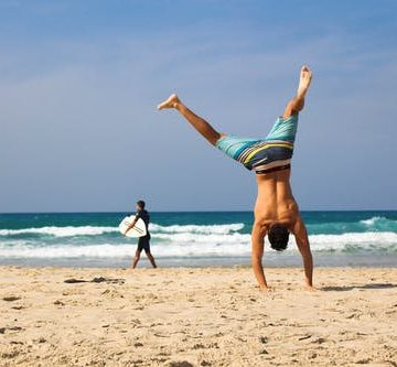 man on beach handstand